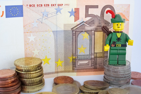 50 euro: Venice, Italy - October 23, 2014: Robin Hood standing on  50 euro bill and European Euro coins