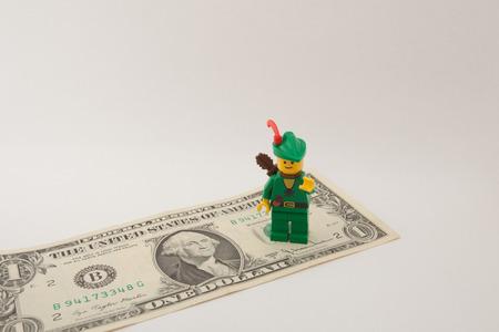 robin hood: Venice, Italy - November 27 - 2014: Robin Hood (as Lego figure) standing on  an American one dollar bill Editorial
