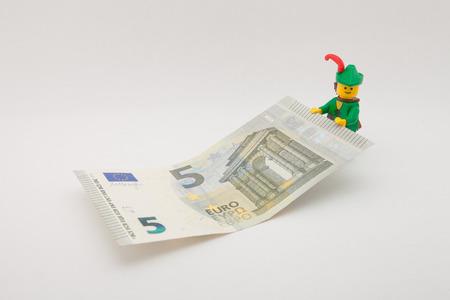 robin hood: Venice, Italy - November 27 - 2014: Robin Hood (as Lego figure) keeping a 5 euro bill