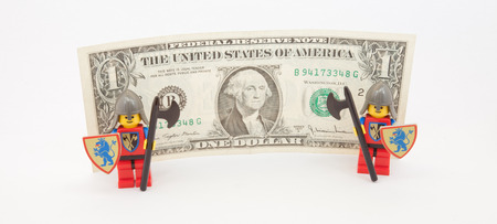 us dollar bill: Venice, Italy - November 27, 2014 - security guards (as Lego figure) standing  next to an US dollar bill
