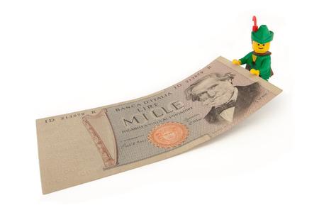 robin hood: Venice, Italy - November 27, 2014: Robin Hood (as Lego figure) keeping an old Italian 1000 Lire bill, November 27, 2014 in Venice, Italy