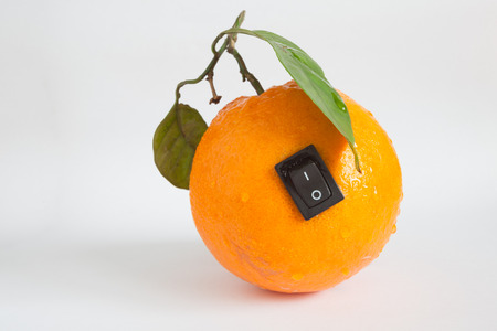 power off: Single orange with switch in power off position on light grey background Stock Photo