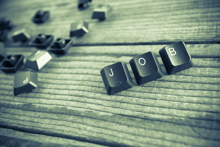 wrote: JOB wrote with keyboard keys on wooden background, green vintage effect