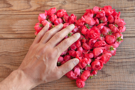 Heart made of red roses in wooden background, covered by an hand to represent personal feelings Stock Photo