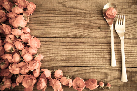 possession: Spoon and fork over a wooden table with red roses, vintage effect