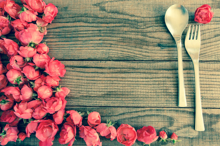 shyness: Spoon and fork over a wooden table with red roses, vintage denim effect Stock Photo