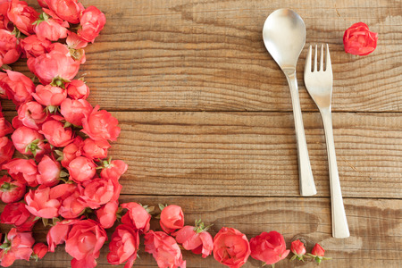 shyness: Spoon and fork over a wooden table with red roses