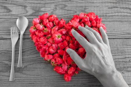shyness: Heart made of red roses in wooden background, covered by an hand to represent personal feelings, black and white effect Stock Photo