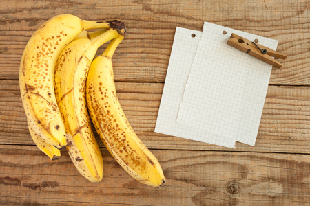 block note: block note on wooden table next to four bananas