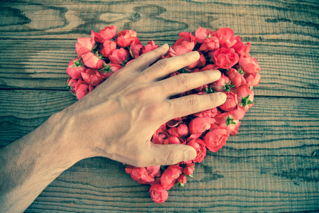 shyness: Heart made of red roses in wooden background, covered by an hand to represent personal feelings, denim effect