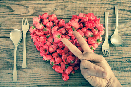 jealousy: Heart made of red roses in wooden background, covered by an hand to represent personal feelings, denin vintage effect