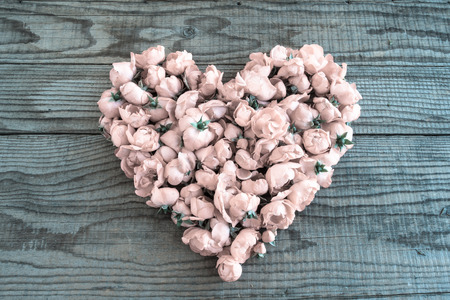 shyness: Heart made of red roses in wooden background to represent personal feelings, denim effect Stock Photo