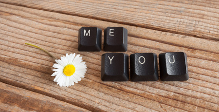 wrote: you and me wrote with keyboard keys on wooden background
