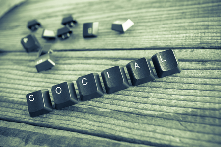 wrote: social wrote with keyboard keys on wooden background, green vintage effect
