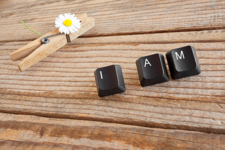 wrote: I AM wrote with keyboard keys on wooden background Stock Photo