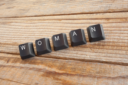 wrote: WOMAN wrote with keyboard keys on wooden background Stock Photo