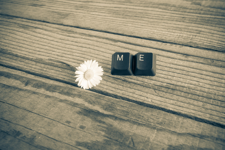 wrote: me wrote with keyboard keys on wooden background, black and white effect