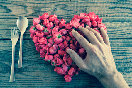shyness: Heart made of red roses in wooden background, covered by an hand to represent personal feelings, denin vintage effect