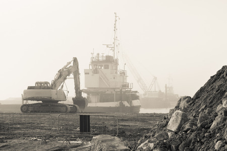 excavator and boat in a construction site, black and white effect Stock Photo
