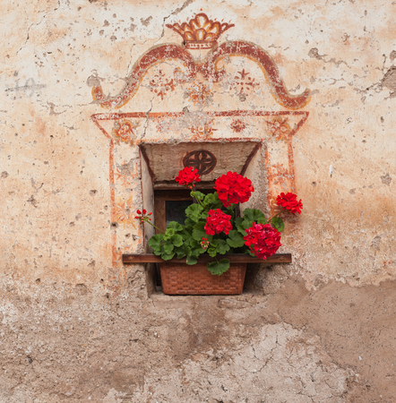 val: Detail of a traditional old balcony  with red geraniums from an old house in St. Magdalena in Val di Funes