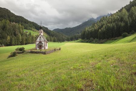 Pequeña iglesia de San Juan entre un amplio prado verde en St. Magdalena, Val di Funes Foto de archivo - 80039070