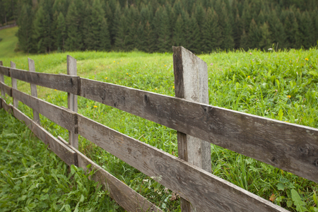 Wooden fence next to  an Italian mountain pasture