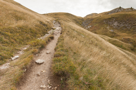 val: walking long a mountain path in Valle di Funes into the Italian Dolomites Stock Photo