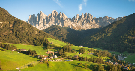 Small Italian mountain town of St. Magdalena in Val di Funes at sunset Imagens