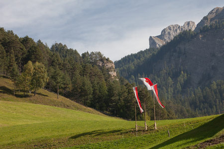 VAL DI FUNES, ITALY - SEPTEMBER 29, 2016:  South Tirol flags on the air during the local celebration Speckfest in Val di Funes