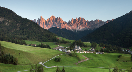 Small Italian mountain town of St. Magdalena in Val di Funes at sunset Editorial