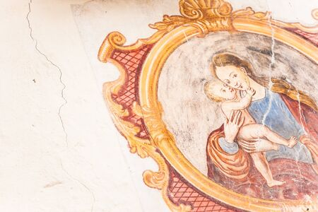 A detail of an old fresco painted on the external wall of the little chapel of St. Johan in Val di Funes Banco de Imagens - 134848758