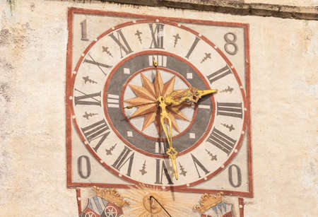 PONTE GARDENA, ITALY - JULY 27, 2017: The clock and its sundial painted outside the bell tower of the church. The history of this paint dates back to the XIX century Banco de Imagens - 142677415