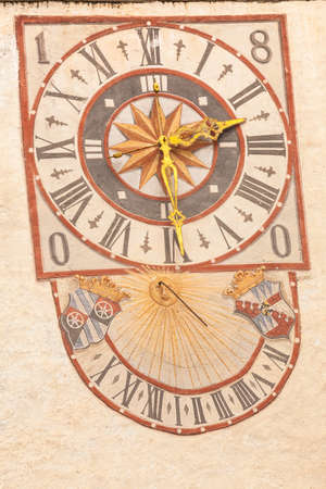 PONTE GARDENA, ITALY - JULY 27, 2017: The clock and its sundial painted outside the bell tower of the church. The history of this paint dates back to the XIX century Editorial