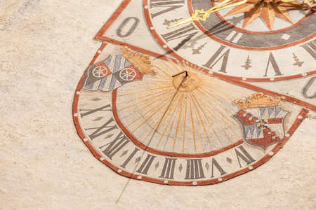 PONTE GARDENA, ITALY - JULY 27, 2017: The clock and its sundial painted outside the bell tower of the church. The history of this paint dates back to the XIX century Banco de Imagens - 142677425