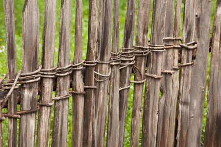 Wooden fence from a green pasture in Val di Funes in Italy