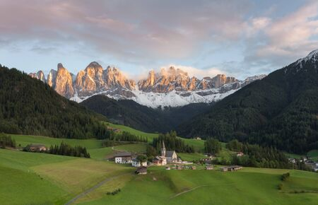 Small Italian mountain town of St. Magdalena in Val di Funes at sunset Banco de Imagens