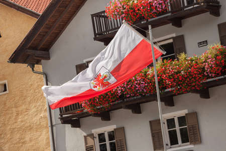 CHIUSA, ITALY - SEPTEMBER 16, 2017: The red and white Alto Adige regional flag is on the wind during the local celebration