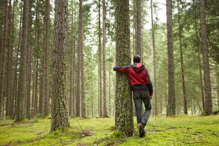 a man hugging a tree in the woods