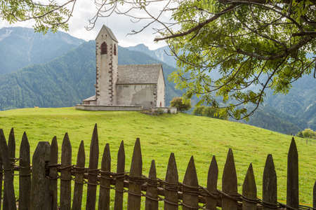 St. Giacomo little church among a wide green meadow in St. Giacomo town, Val di Funes