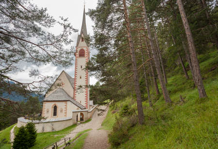 St. Giacomo little church among a wide green woods in Val Gardena area