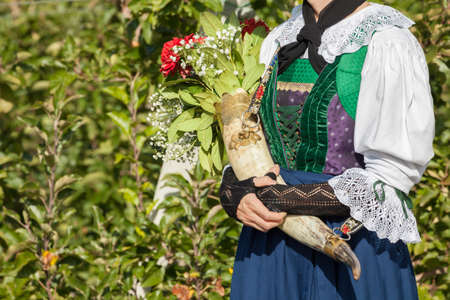 A girl in typical costume during an autumn local celebration in Val Isarco (South Tyrol)