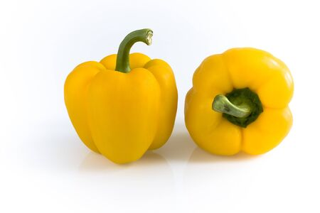 Two yellow peppers isolated on white background. Still life picture taken in studio with softbox.