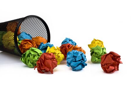 Multi colored paper balls all around a black recycle bin. Picture taken in studio with white background ad softbox.