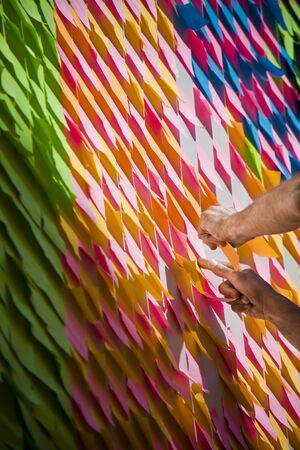 Human hands covering a wall with colorful sticky notes