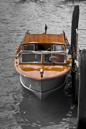 Luxury wooden speedboat with teak deck, moored in a canal of Venice - Italy