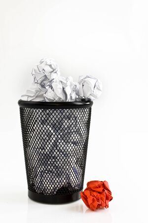 Red paper ball and basket full of white paper balls, isolated on white background. Picture taken in studio with soft-box.