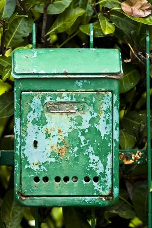 Rusty green mailbox stuck to the house gate