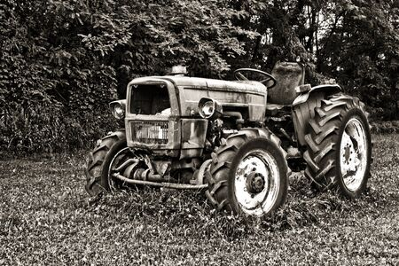 Rusty tractor abandoned in a field - Black and white image