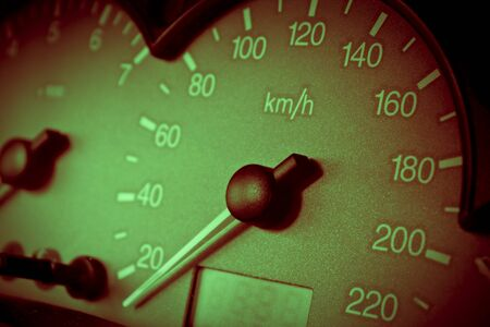 Close up picture of a car dashboard with speedometer showing speed in Km/h