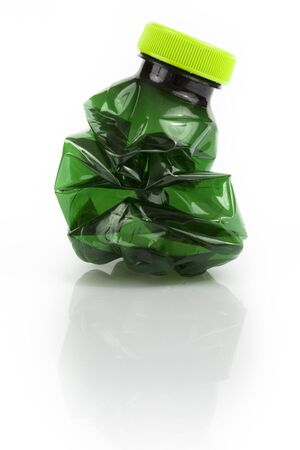Crushed dark green plastic bottle on white background. Still-life picture taken in studio with soft-box.